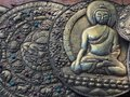 An image of a seated Buddha on a bronze metal plate, a wall decoration.
