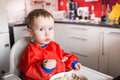 Image showing a little blond and blue eyed boy eating lunch on his own in the kitchen Stock Photo