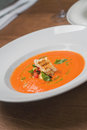 Image of tasty pumpkin soup with crouton and basil served in res close orange bread on table Stock Photography