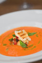 Image of tasty pumpkin soup with crouton and basil served in res close orange bread on table Stock Photo