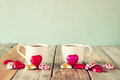 Image of two red heart shape chocolates and couple cups of coffee on wooden table valentine s day celebration concept vintage Stock Photos