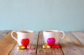 Image of two red heart shape chocolates and couple cups of coffee on wooden table valentine s day celebration concept vintage Stock Photo