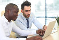 Image of two young businessmen interacting at meeting in office Stock Images
