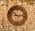 An image of a very old clock on a brick wall Royalty Free Stock Photo
