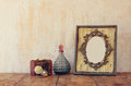 Image of victorian vintage antique classical frame, jewelry and perfume bottles on wooden table. filtered image Royalty Free Stock Photo