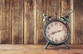 Image of vintage alarm clock on wooden table in front of wooden background. retro filtered