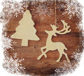 Image of wooden decorative christmas tree and reindeer hanging on a rope over wooden background with snowflake overlay. Royalty Free Stock Photo