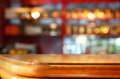 Image of wooden table in front of abstract blurred background of restaurant lights Royalty Free Stock Photo