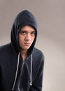 Image of young man in hooded sweater sad Stock Image