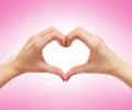 Imagem do fim acima das mãos fêmeas em uma forma de um coração Imagens de Stock