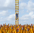 Imagination freedom with a creative businessman climbing out of a chaotic pencil landscape using a ladder made of yellow pencils Royalty Free Stock Photography