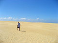 Img man walking alone in the sand with blue sky Royalty Free Stock Photo