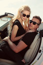 Impassioned couple in casual clothes posing in luxurious car love story fashion outdoor photo of Stock Images