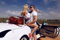 Impassioned couple in casual clothes posing beside luxurious car love story fashion outdoor photo of Stock Photography
