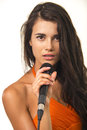 Impassioned girl in orange shirt with microphone lovely brunette expressive eyes is holding on the white background woman Royalty Free Stock Photography
