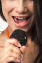 Impassioned lady in orange shirt with microphone lovely brunette expressive lips is holding on the white background Royalty Free Stock Photo