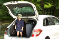 Impatient little boy ready for his vacation wearing trendy sunglasses standing up in the open back of a hatchback car with Royalty Free Stock Photo