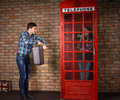 Impatient man pointing to his watch men as he stands alongside a red british telephone booth with suitcase while wife chats Royalty Free Stock Photo