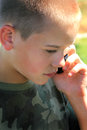 Important call a closeup of a cute teenaged boy with short hair wearing a camo shirt talking on the phone shallow depth of field Stock Photos