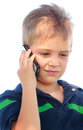 Important call a closeup of a cute young boy with short hair wearing a striped shirt talking on the phone shallow depth of field Stock Photos