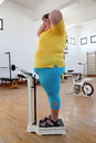 Impressed overweight woman on scales in gym Royalty Free Stock Photo