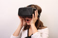 An impressed surprised flabbergasted woman taking off or putting on oculus rift vr virtual reality headset a wearing she s with Stock Images
