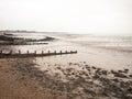 Impressive overcast seaside beach scene groynes pebbles mudflats Royalty Free Stock Photo