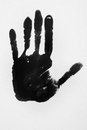 Imprint of a hand with black paint and background gray Royalty Free Stock Photography