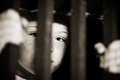 Imprisoned child behind bars single abused male with part of face obscured in shadows of jail cell and hands Stock Images