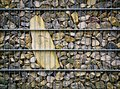 Imprisoned stone background or texture in steel mesh Stock Image