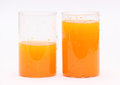 Improper nitrition concept fresh orange juice in two glasses with water droplets and fresh cold drink but imbalanced with half Royalty Free Stock Images