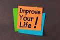 Improve your life colorful notes pasted on blackboard background Stock Photography