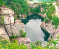 Inactive used granite quarry reflections in the water at the bottom of a Royalty Free Stock Photo