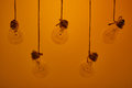 Incandescent light bulbs hanging on a yellow background Royalty Free Stock Photo