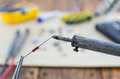 The incandescent soldering iron and the resistor workplace angle view Royalty Free Stock Photo