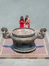 Incense burner angle view of praying young women standing in front of the Royalty Free Stock Image