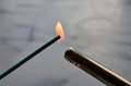 Incense stick being lit with a flame from a lighter Royalty Free Stock Photo