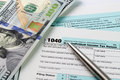 Income tax filing filling out forms with us dollar and pen Royalty Free Stock Photo