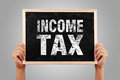 Income tax hands holding small blackboard with text against gray background Stock Photos