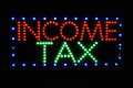 Income tax sign in colorful red green and blue lights Stock Image