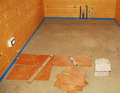 Incomplete floor tiling a concrete in a newly built wooden fir house which is about to be tiled the blue foam material is Royalty Free Stock Images