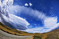 Incredible clouds gray dirt road in the chile national park torres del paine shaped formed by glaciers glisten in the sun picture Royalty Free Stock Photography