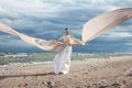 Incredible portrait of model with extremely long dress at the beach outdoors Royalty Free Stock Photo