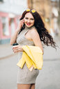 Incredibly beautiful girl wearing a dress at the throat, trendy yellow jacket, with a cup of coffee talking on the phone Royalty Free Stock Photo