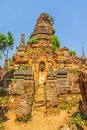 Indein inle lake ruined statue at the entrance of the ancient stupas at overgrown with plants myanmar Stock Photo