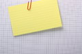 Index card and graph paper background a yellow clipped with a paperclip to a grey lined sheet of with copy space Stock Image
