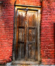 Indian architecture ancient wooden door a locked which is a part of with red colored wall Royalty Free Stock Photo