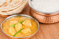 Indian chicken curry meal with rice parotta bread served in authentic copper utensils green chilli used as garnish Stock Image