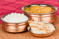 Indian chicken curry meal with rice parotta bread served in authentic copper utensils green chilli used as garnish Royalty Free Stock Photos