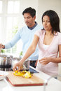 Indian couple cooking meal at home in kitchen Stock Photos